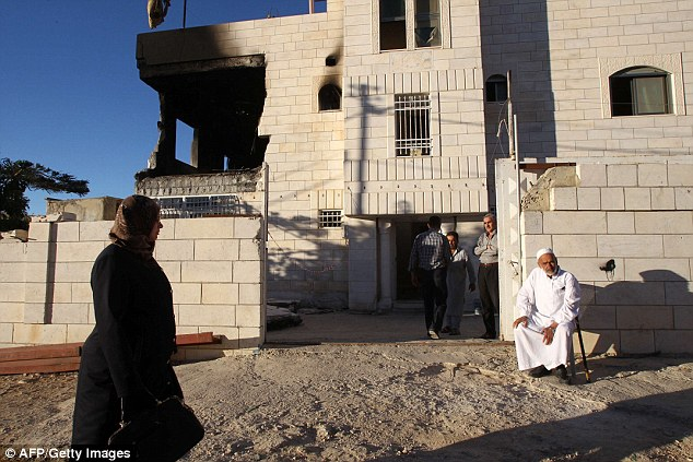 Relatives: Family members gather outside the house of Amer Abu Eishe after it was virtually destroyed by an explosion detonated by the Israeli army in the early hours of this morning