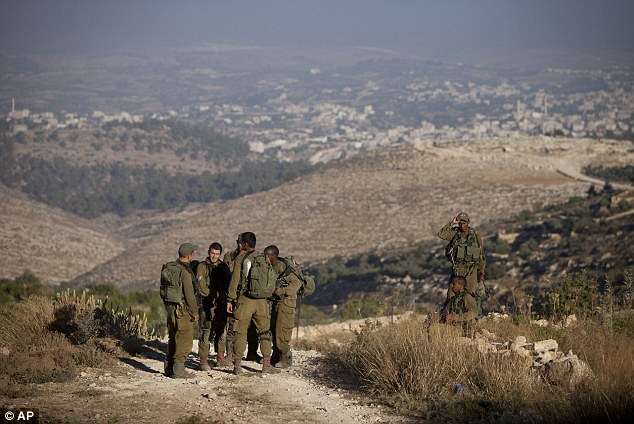 Location: Israeli soldiers stand near the area where the three Israeli teenagers' bodies were found yesterday. The rural track is just outside the village of Halhul, a few miles north of the West Bank city of Hebron