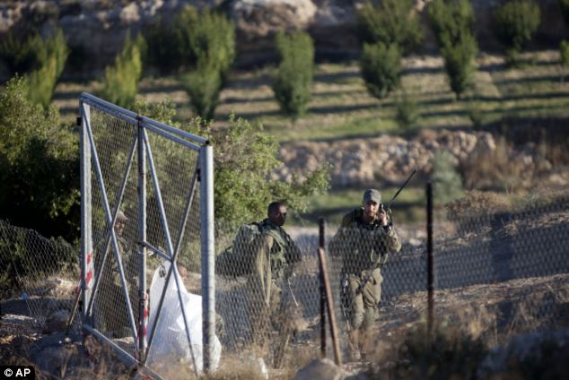 Discovery: Israeli soldiers patrol close to the area where the bodies of the three Israeli teenagers were found