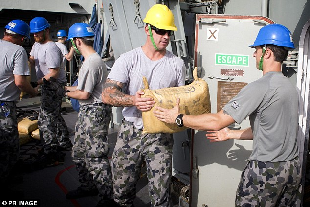 Petty Officer Boatswain Ewen Jenkins (second from right) assists with the loading of the seized hashish onboard HMAS Darwin