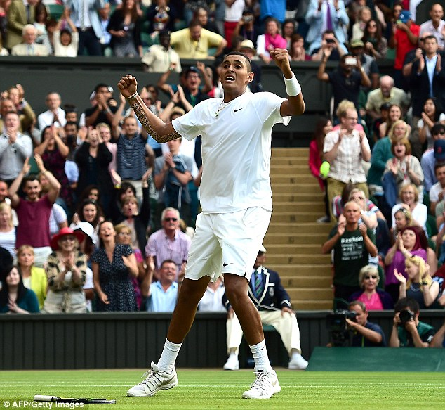 Australian tennis star Nick Kyrgios drops his racket in disbelief after beating world number one Rafael Nadal 7-6, 5-7, 7-6, 6-3 during the fourth round at Wimbledon