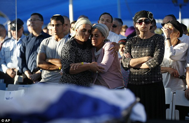 Support: Bat-Galim Shaer, front right, and Iris Yifrah, front 2nd right, mothers of two of the three teens, embrace during the funeral
