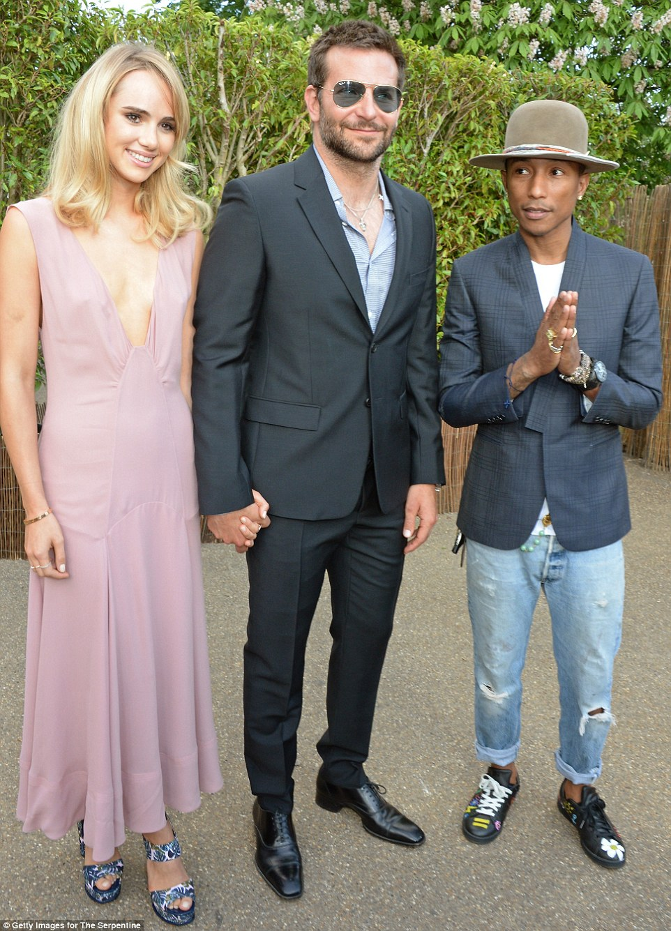 Three's company: Brad and Suki are joined by pint-sized pop star Pharrell Williams as they pose up prior to the Serpentine's summer party