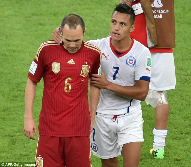 Tough time: The Spain midfielder is consoled by Barca teammate Alexis Sanchez after the World Cup exit