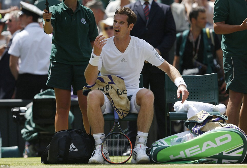 Not happy: Murray was sheltered from the sun by a ball boy holding an umbrella during a break from the action on Centre Court