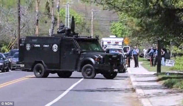 Tense: An armored vehicle and SWAT team surround a Rapid City house on Tuesday after a burglar took a two-year-old boy hostage