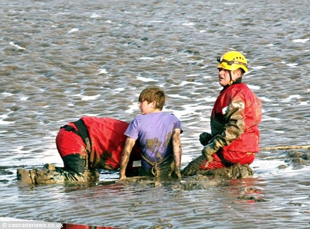 Stuck in the mud: Kavan Humphreys, 13, got stuck while looking for a place to fish in Morecambe Bay, Cumbria