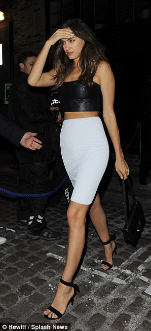 Lean limbs: Irina added even more height to her slender legs with a simple pair of black strappy heels while she accessorised with a plain black bag