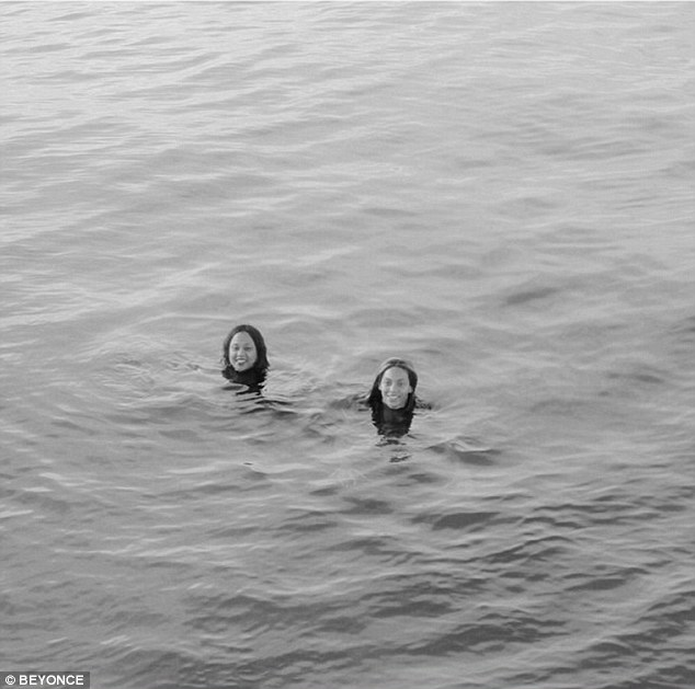 The good life: Beyonce grins as she enjoys a dip in the ocean with a friend