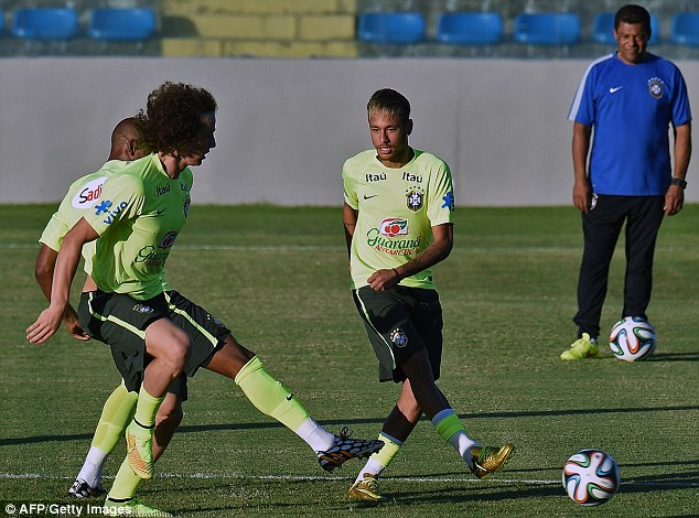 Battle: Neymar plays the ball on as David Luiz and Fernandinho make a late challenge during training