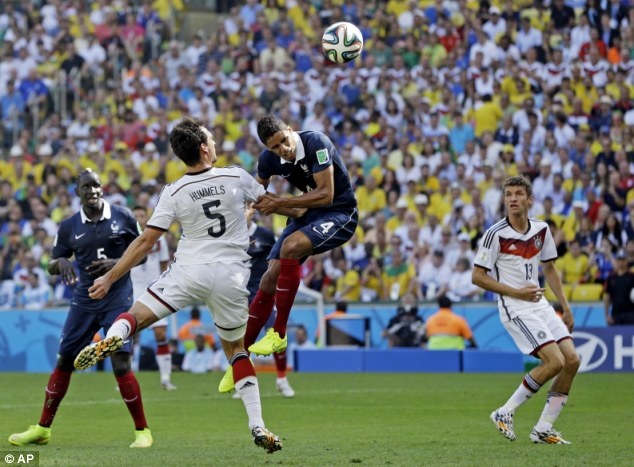 Bullied: Varane is pushed away from the ball as Mats Hummels heads Germany in front