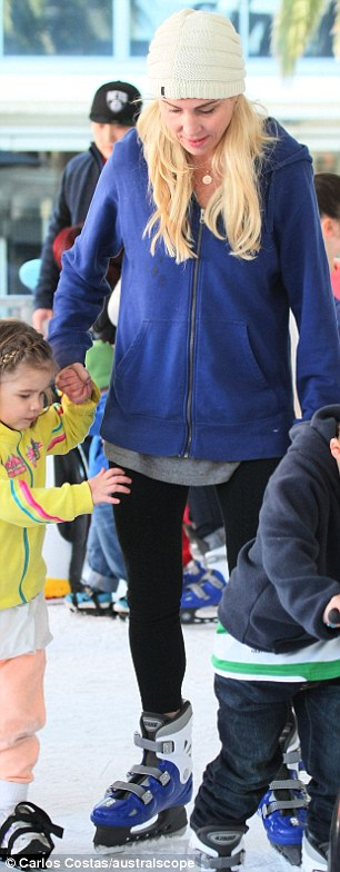 Get yer skates on! The former professional swimmer guided her youngest daughter Capri, 3, around the ice rink, she braved the cool climes in a cream beanie and blue hoody