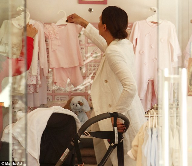 Protective: The new mum kept one hand on the pram even when she was taking a look at cute pink dresses