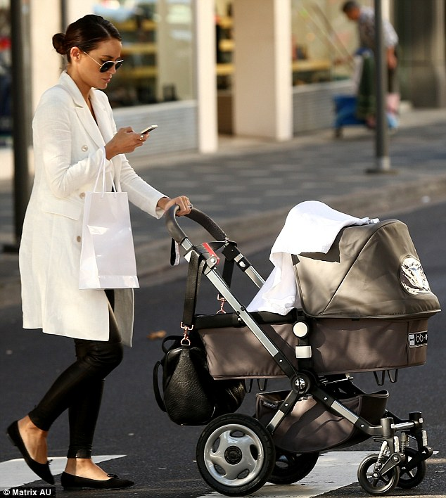 Multi-tasking: The new mum has no problem with juggling shopping with walking, pushing the pram and texting