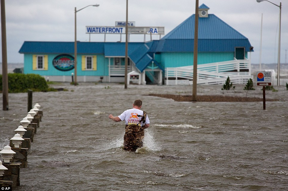 Several feet of coastal flooding deluged the Outer Banks of North Carolina on Thursday night - damaging homes and businesses. Bryan Wilson, the owner of Miller's Waterfront Restaurant, wades up to his damaged storefront