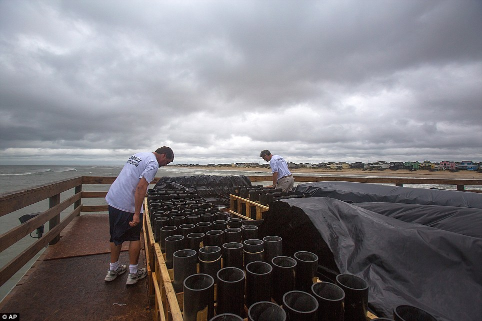 Down, but not out: Pyro-technicians of Zambelli, Bryan Jackson, left, and Steve Neer, check water damage to fireworks barrels at the Nags Head Fishing Pier as the low clouds of Hurricane Arthur pass through Nags Head, N.C. Friday, July 4, 2014