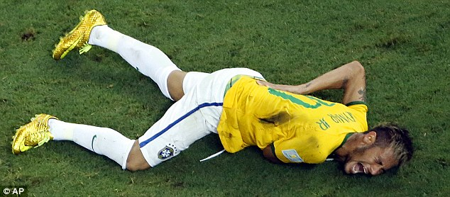 Agony: Neymar clutches his back after going down injured during Brazil's win over Colombia