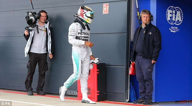 Lonely walk: Lewis Hamilton trudges back to the pit lane after qualifying for the British Grand Prix