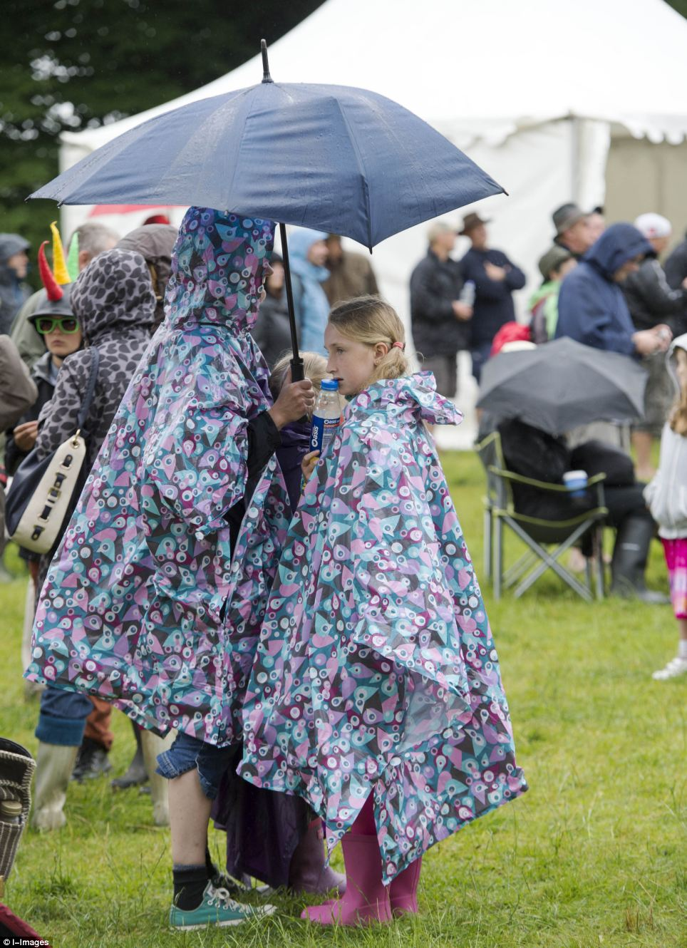 Matching coats: These two festival-goers at the Cornbury Music Festival in Chipping Norton, Oxfordshire, brighten up a bleak day in patterned purple rain coats