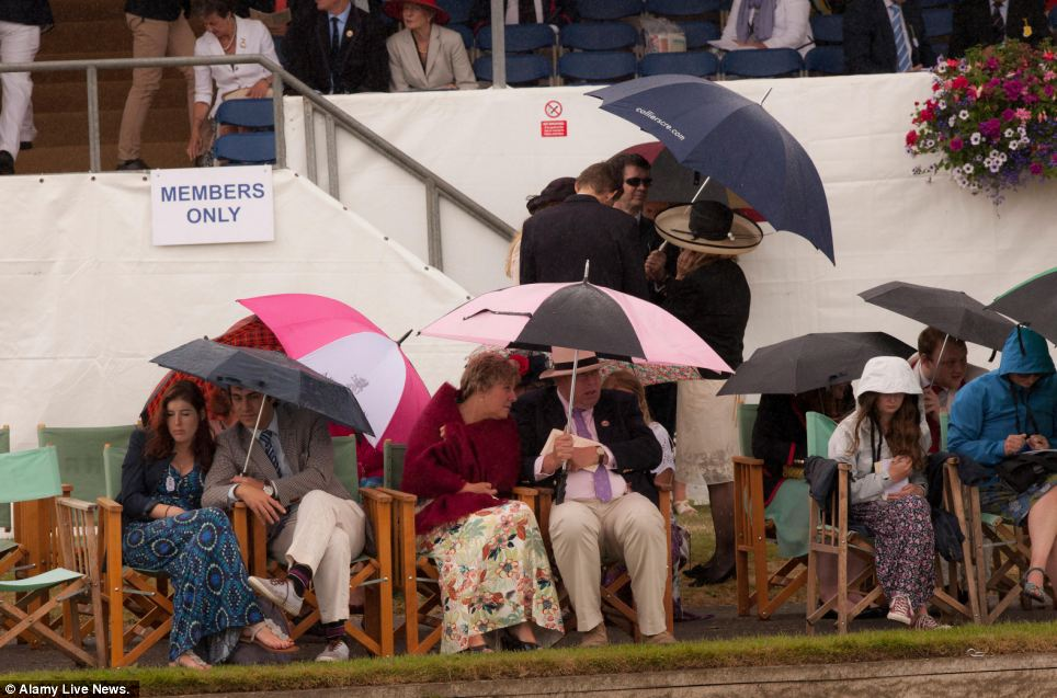 Wet on the waterside: Summer dresses are covered up with jumpers and raincoats as spectators take in the action at the Henley Royal Regatta in Oxfordshire