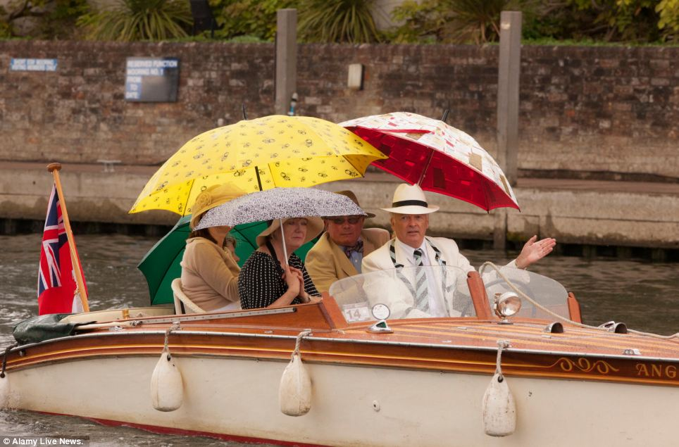 Wet weather: People at the Henley Royal Regatta shelter under umbrellas as the weather takes a turn for the worse