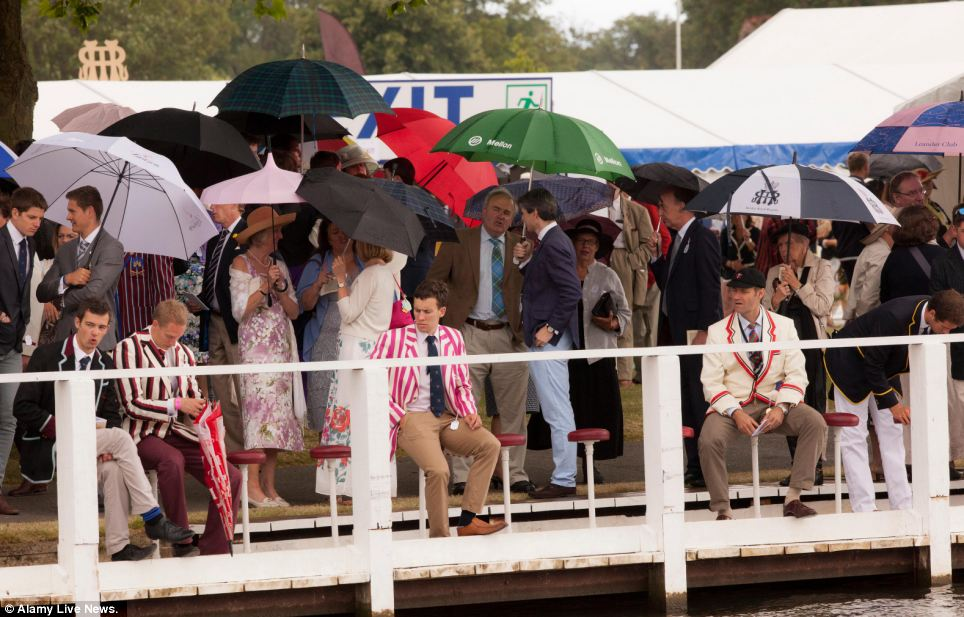 Brollies and boat jackets: Pastel-striped jackets add a splash of colour as spectators gather to watch the Henley Royal Regatta in Oxfordshire
