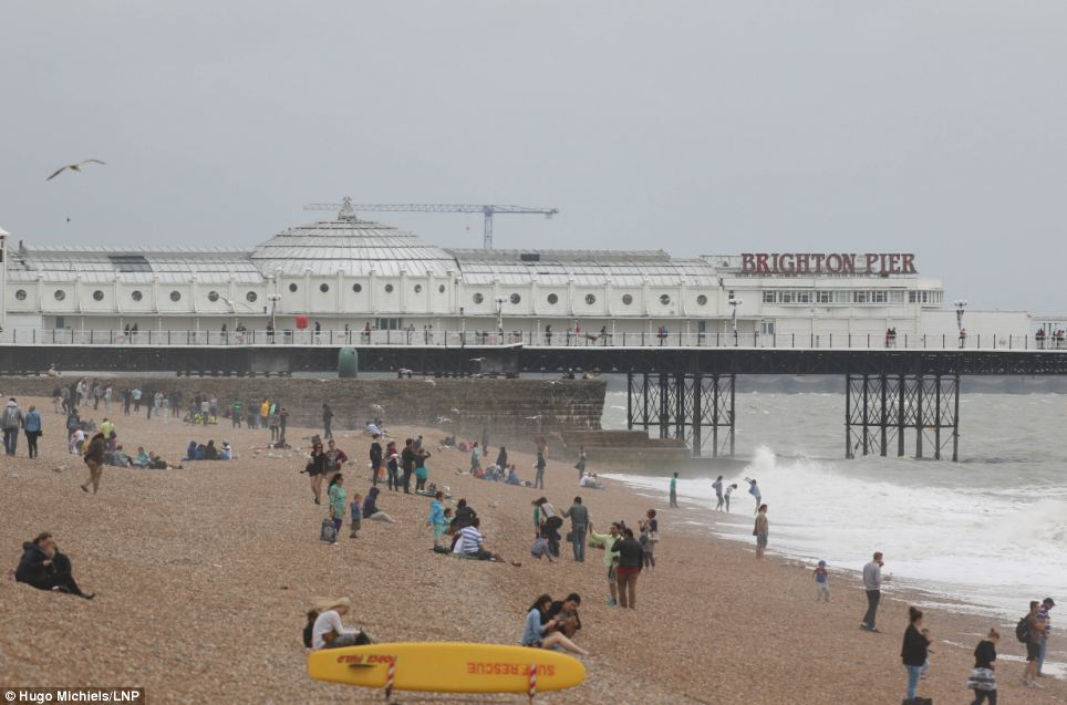 Reduced numbers: The number of people on Brighton beach was drastically lower today as the warm, sunny weather gave way to downpours
