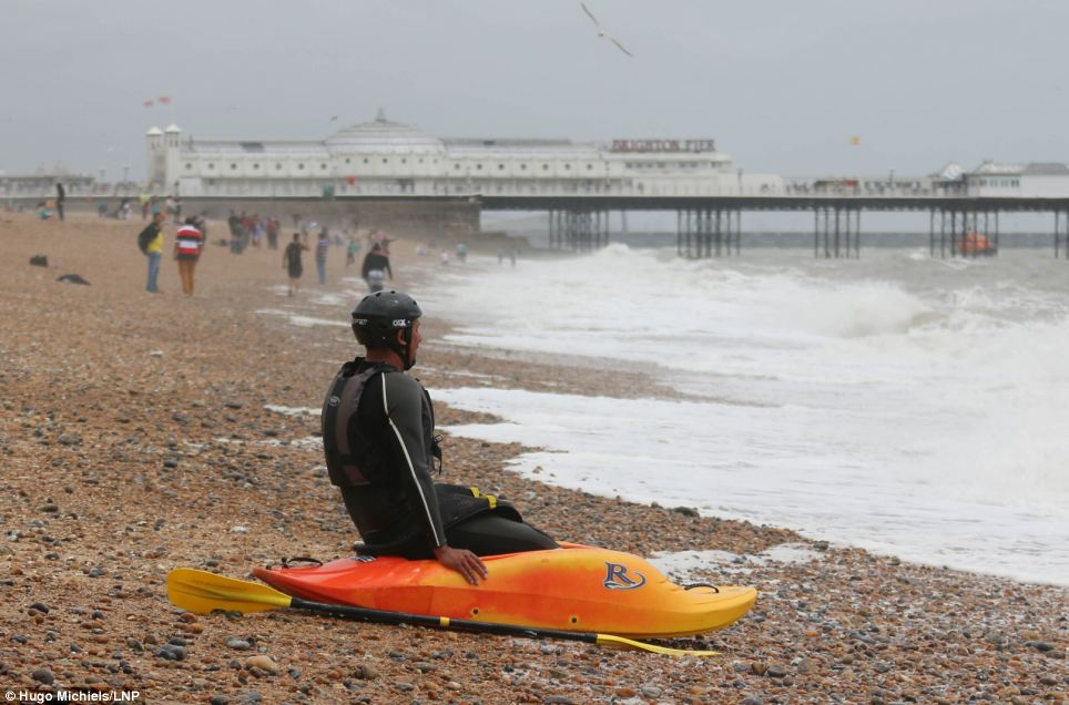 A man in a kajak is pictured on Brighton Beach today. Rain and clouds has stopped most people from visiting the South Coast while rough seas dettered people from swimming