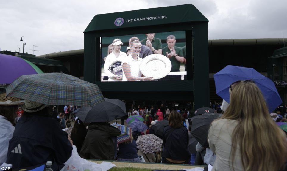 Murray Mound: Tennis fans huddle under umbrellas and raincoats to watch Petra Kvitova of the Czech Republic win the women's singles final at Wimbledon