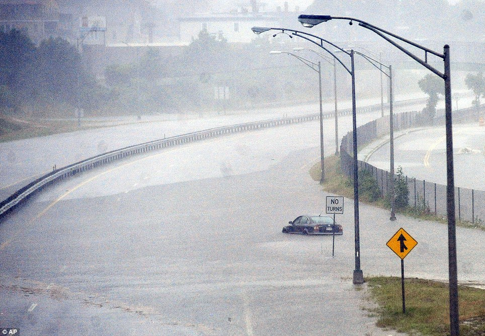 Flood: A vehicle  sits in the flooded waters of the closed Route 18 on Friday, July 4, 2014, in New Bedford, Massachusetts, after heavy rains from Arthur