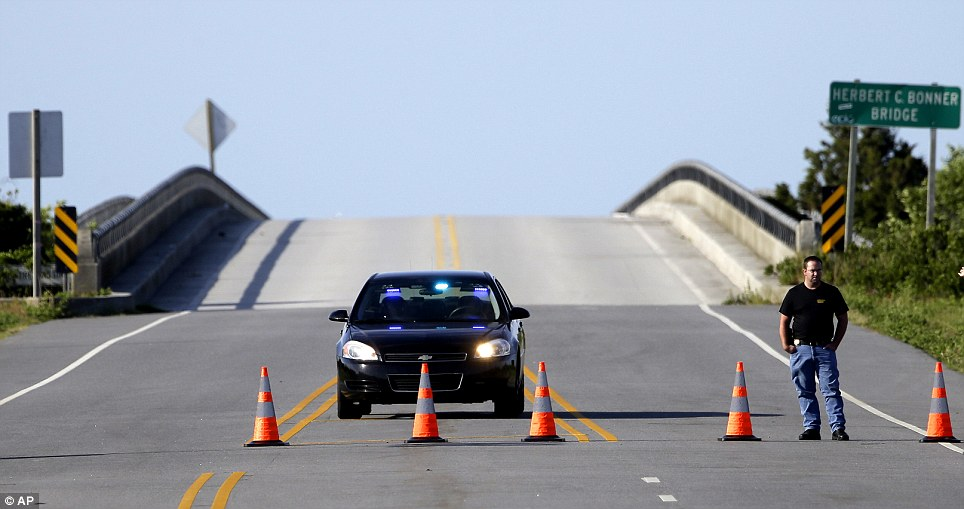 Saftey: A police checkpoint prevents traffic from crossing a briudge while inspections continue following Hurricane Arthur's impact on the Outer Banks near Nags Head, North Carolina on Saturday