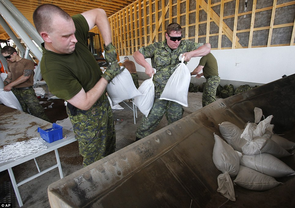 Working together: Military from Shilo work to fill and load sandbags in Portage La Prairie, Manitoba, on Saturday