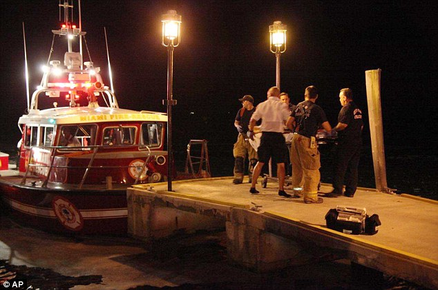 In a hurry: Emergency workers carry an injured person on a stretcher on Friday night, July 4, 2014 after three boats collided near a Miami marina around the end of a fireworks display