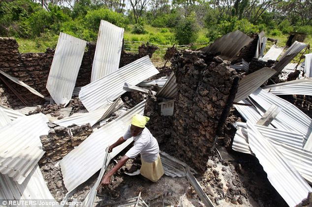 A woman rummages through ruins of her home burned down when gunmen torched a Hindi trading centre