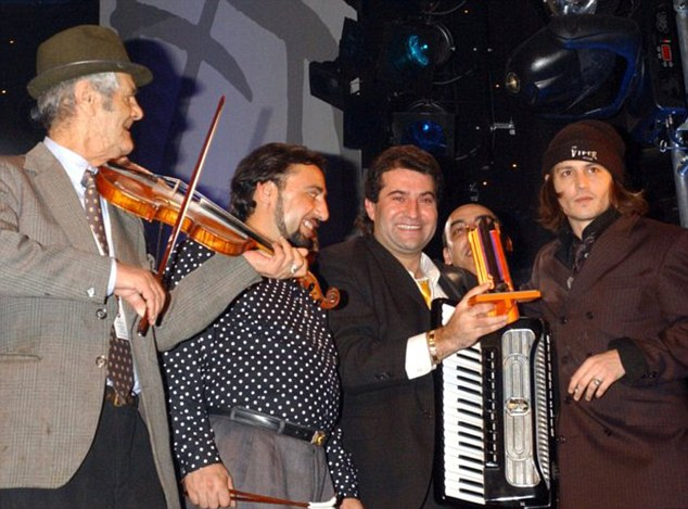 Although Ionita (third from right) performs in Hollywood films and mingles with the likes of Johnny Depp (far right), his daughter is begging in Britain and earning £60-a-day