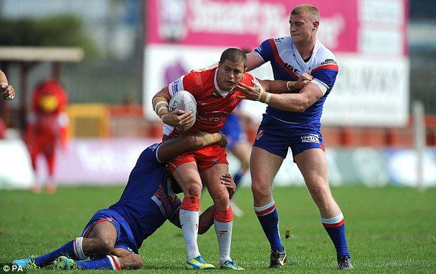 Standing strong: Hull KR's Travis Burns is tackled by St Helen's Luke Thompson (right)