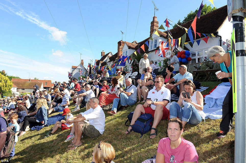 Nice day for it: Cycling fans wait in Finchingfield for the Tour de France to arrive as it heads from Cambridge into London on stage three of the cycle race