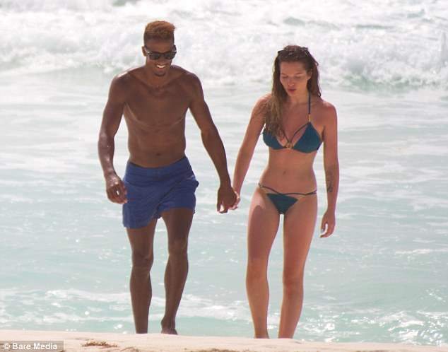 Hand-in-hand: Flanagan and Sinclair looked to be having fun in the sun as they took to the beach in Mexico