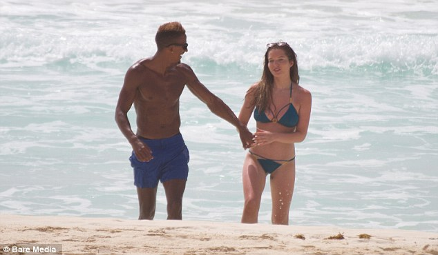 Having a laugh: Scott also showed off his buff body as he walked across the beach with the brunette stunner