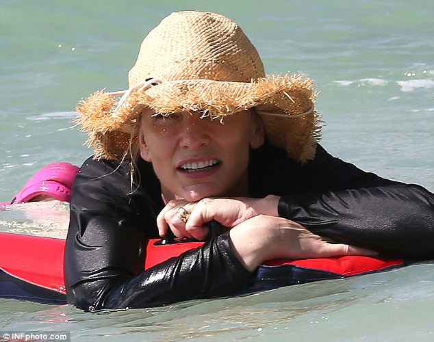 Hat you Cate? The Oscar-winner shielded herself against the sun in floppy head gear and rash top as she bobbed around in the sea