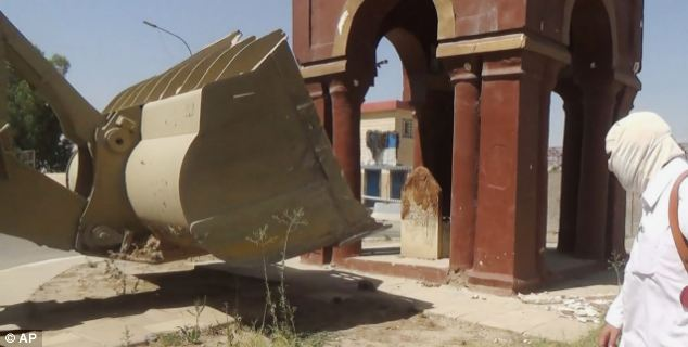 A bulldozer edges closer to a monument called 'The Girl's Tomb' in Mosul, Iraq
