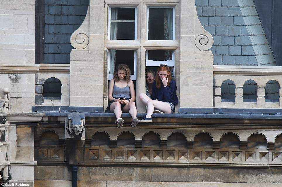 Dangerous: Two young women sit precariously on a window ledge as they wait for the Tour de France to go through Cambridge