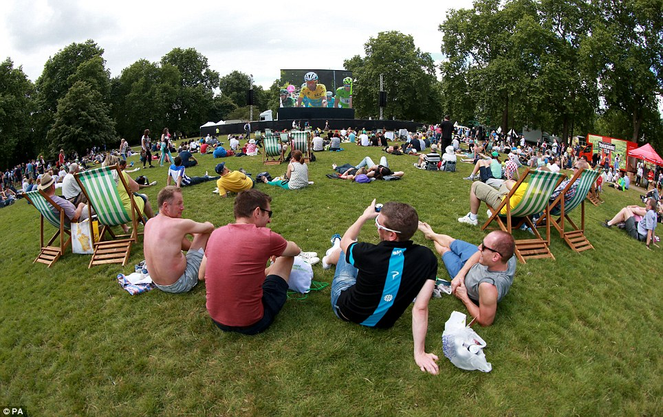 Sitting back: Spectators in St James' Park watch the start of stage three of the Tour de France on a giant screen