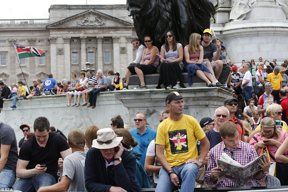 Getting a good seat: Thousands of people sit next to the Tour de France route in Central London to watch the arrival of the third stage
