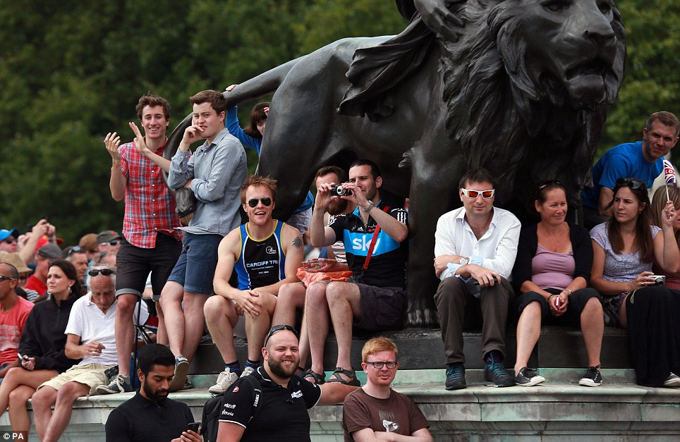 Taking a photo: Fans gather around Buckingham Palace in preparation for stage three of the Tour de France that will finish in London later today