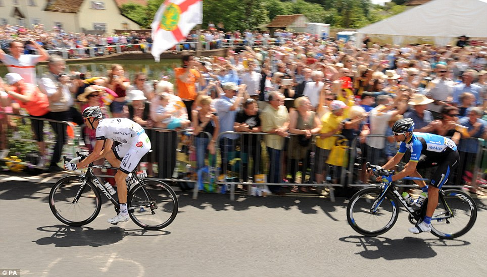 At speed: Crowds greet the breakaway riders as they arrive in the village of Finchingfield in north Essex during stage three