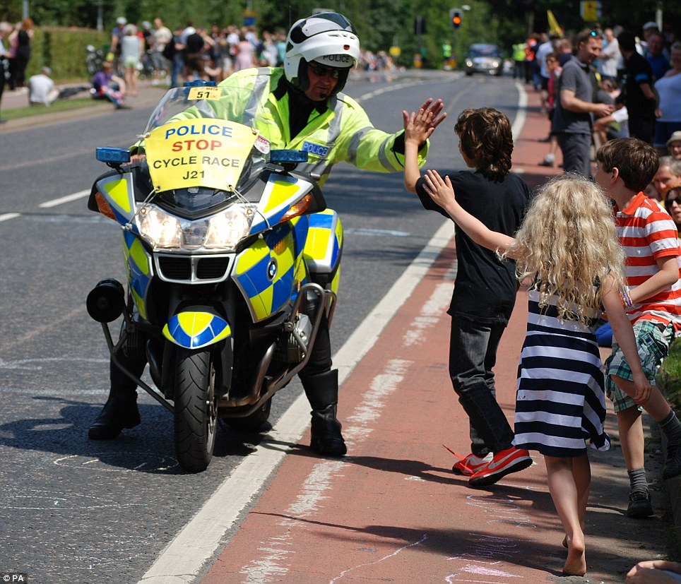 Interaction: A police officer high-fives children as they wait for the riders to come pass outside Cambridge during stage three of the Tour de France