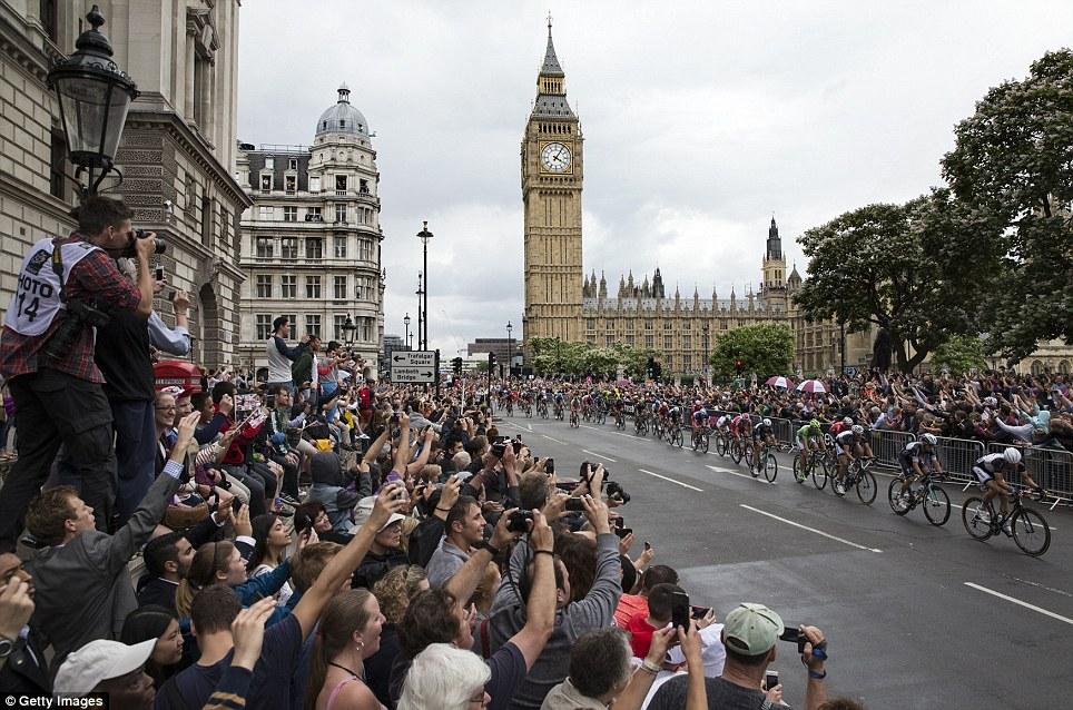 Packed in: Crowds cheer as cyclists competing in the Tour de France pass through Parliament Square at the end of the race's third stage