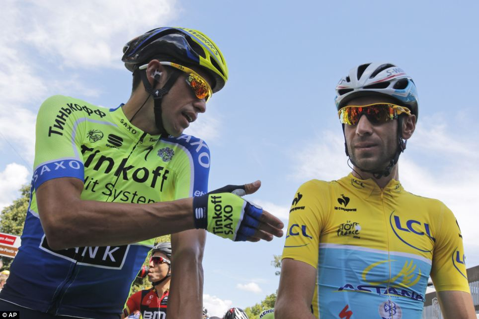 Focus:  Spain's Alberto Contador gestures when talking to Italy's Vincenzo Nibali, wearing the overall leader's yellow jersey, prior to the start of the third stage of the Tour