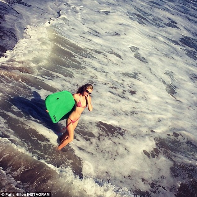 'Ready to #killit in the waves': Paris donned a pink string bikini for her body-boarding fun on the beach